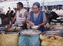Una boliviana en su puesto, abierto con microcrédito.
