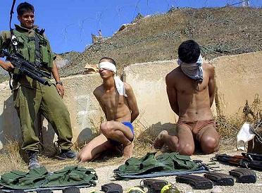 Un soldado israelí vigila a dos palestinos detenidos cerca de un asentamiento judío en Gaza